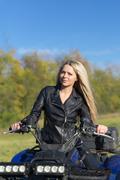 Elegant woman riding extreme quadrocycle ATV - stock photo