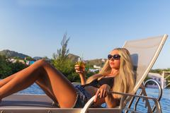 Young slim woman glass juice sunbed near swimming pool Stock Photos