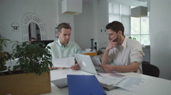 Pair of marketer looking on graphs and charts discussing results of sales - stock footage