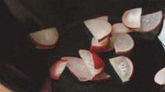 Slices of radish fall into black salad bowl Stock Footage