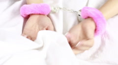 female hands in leather handcuffs. sex toys. grabs the white sheets. pink fur - stock footage