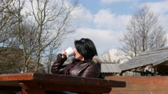Brunette woman drinking coffee in a bar outdoors in a sunny day - stock footage