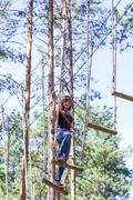 Young brave woman climbing in a adventure rope park Stock Photos