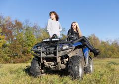 Two elegant women riding extreme quadrocycle ATV - stock photo