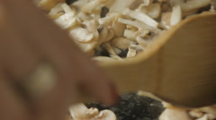 Girl's hands fry mushrooms on a cast-iron frying pan Stock Footage