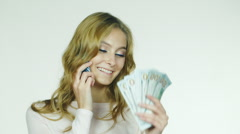 Attractive woman speaking on the phone in his hand holds a fan of money Stock Footage