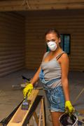 Pretty young woman builder with brush and paint - stock photo