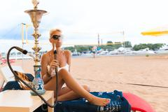 Woman with hookah on the beach in bikini Stock Photos
