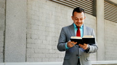 Caucasian businessman writing in notepad outdoors Stock Footage