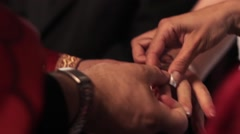 Godmother put to indication of the priest wedding ring on bride's finger Stock Footage