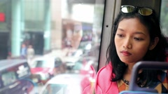 Woman in a bus looking out the window at traffic jam in city Stock Footage