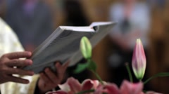 Priest reads the holy book during evening Mass Stock Footage