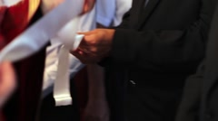 Priest stretches a white ribbon from grooms to godparents during religious - stock footage