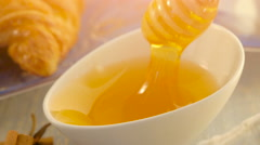 Honey with wooden honey dipper and ceramic bowl Stock Footage