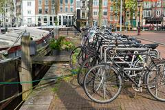 Bicycles next to canal of Amsterdam Stock Photos