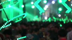 Crowd of people enjoying open air concert colorful green light and water spray - stock footage