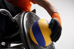 The man on the sports wheelchair with the ball - stock photo