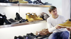 Man chooses winter shoes at fashionable shop Stock Footage