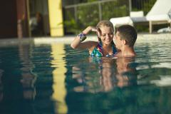 Young, sexy and attractive couple coming into swimming pool in sexual embrace - stock photo