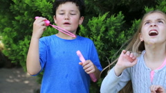 Cute kids blowing a soap bubbles in park - stock footage