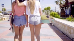 Back side of two girls with skateboards Stock Footage