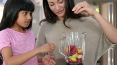 Mother and daughter cooking fruit in the kitchen Stock Footage
