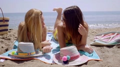 Two attractive young women laying sunbathing Stock Footage