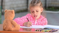Five-year girl with enthusiasm draws a teddy bear sitting in front of her Stock Footage