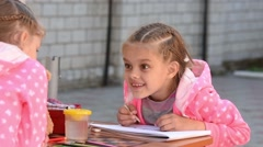Seven-year girl drawing in an album emotionally speaks with another girl - stock footage