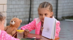 Seven-year girl painted on the album shows another child Stock Footage