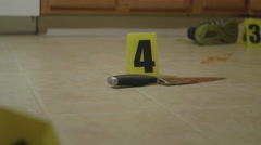 Dolly Shot of Bloody Knife on Floor with Crime Scene Markers Stock Footage