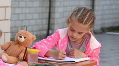 Seven-year girl with enthusiasm draws a pencil on the album, doing drawing with - stock footage