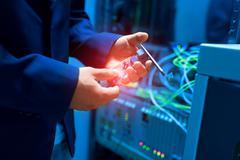 People fix node fiber optic in network room - stock photo