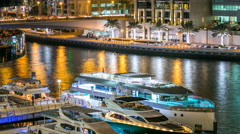 View of Dubai Marina Towers and yachts in canal in Dubai night timelapse Stock Footage