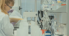 Woman scientist pouring liquids into tubes  Stock Footage