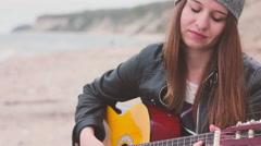 A girl plaing guitar on the wild beach Stock Footage