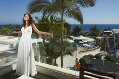 Divine, gorgeous bride standing and posing on the balcony of the hotel under  - stock photo