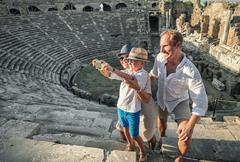 Young positive family take a self photo on the antique sights in Side, Turkey - stock photo