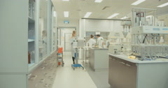 Lab technician pushing equipment in a lab Stock Footage