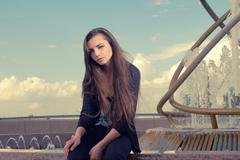 Young woman wearing a black wear is sitting by a fountain in the city and Stock Photos