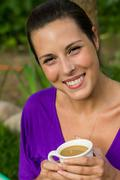 Beautiful young woman drinking coffee outdoors - stock photo