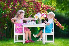 Kids having fun at garden tea party - stock photo