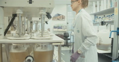 Lab technician conducting experiments in a pharmaceutical research laboratory Arkistovideo