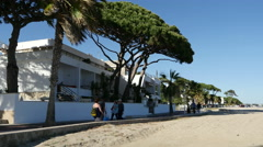 Spain Cambrils people on a shady path by a sandy beach Stock Footage
