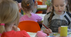The Girl With Pigtails Concentrates at the Task. Stock Footage