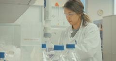 Lab technician pouring chemicals to glassware in a lab Stock Footage