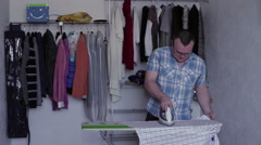 Man iron to iron a man's shirt on the ironing Stock Footage