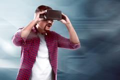 Asian man watching something on virtual reality headset Stock Photos