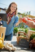 Friendly woman tending an organic vegetable stall at a farmer's market and Stock Photos
