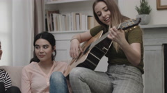 Group of female friends play guitar in student room Stock Footage